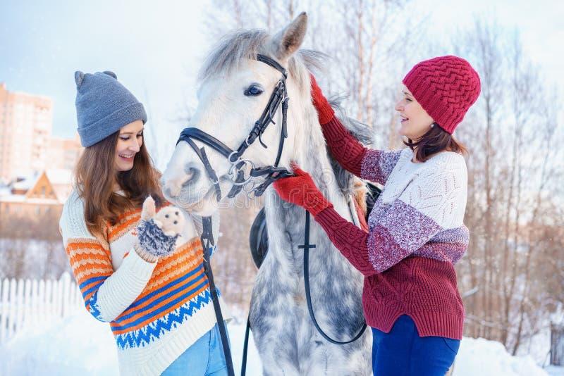 母亲和女儿在与一个美丽的白马的冬天 图库摄影