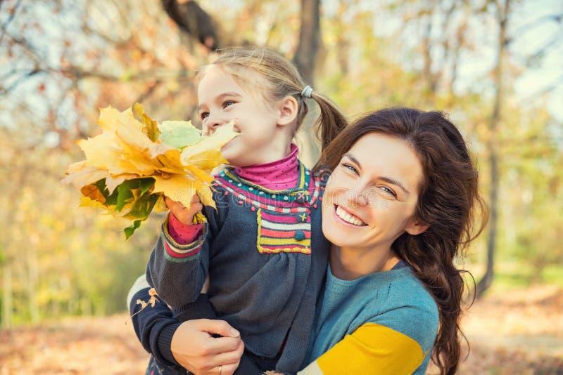 母亲和女儿在公园享受晴朗的秋天 库存照片