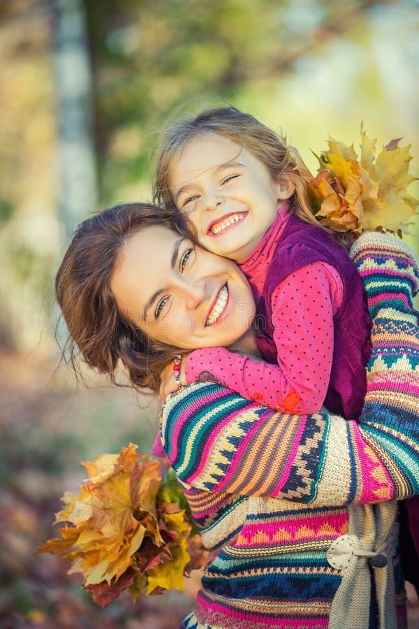 母亲和女儿在公园享受晴朗的秋天 免版税图库摄影