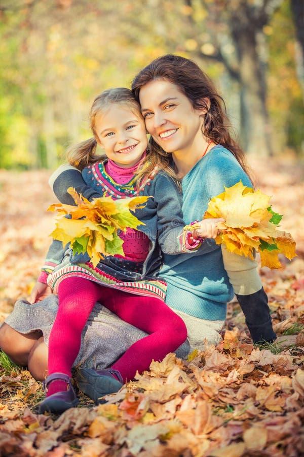母亲和女儿在公园享受晴朗的秋天 免版税库存图片