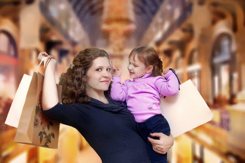 母亲和女儿在商店 免版税库存图片