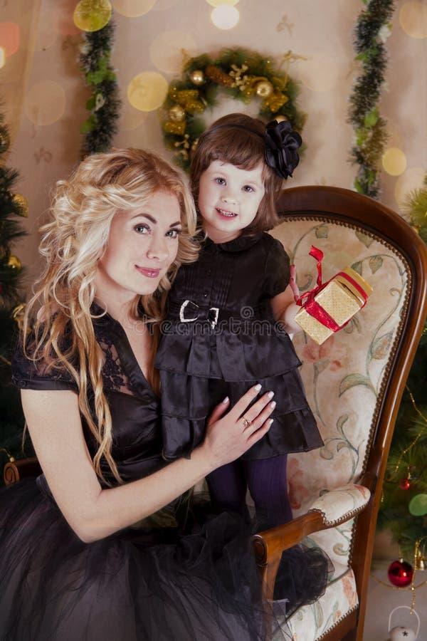 母亲和女儿在圣诞树下 免版税图库摄影