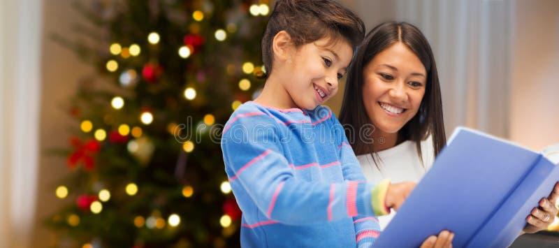 母亲和女儿在圣诞节的阅读书 库存图片