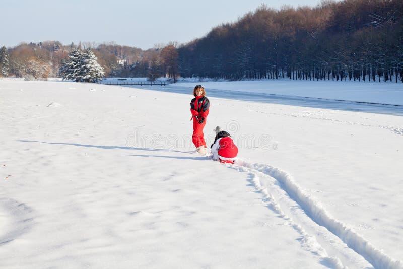 母亲和女儿在多雪的冬天公园 免版税图库摄影
