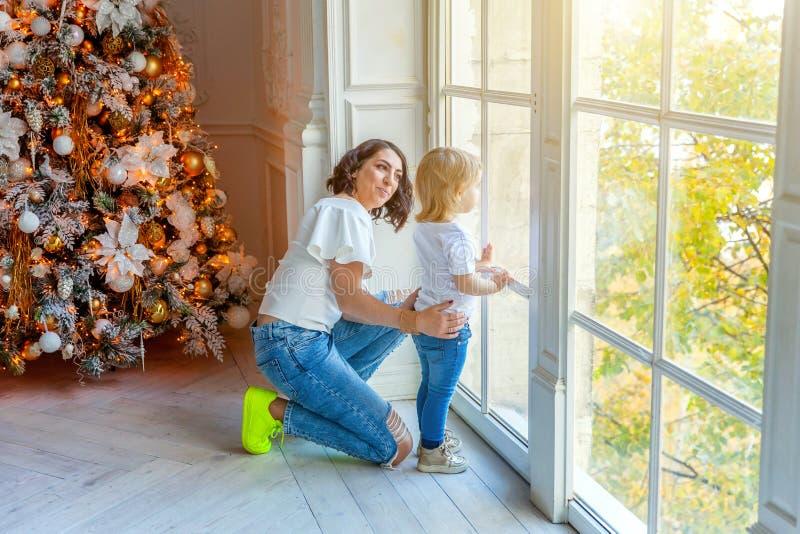 母亲和女儿在大窗口和圣诞树附近在家 免版税图库摄影