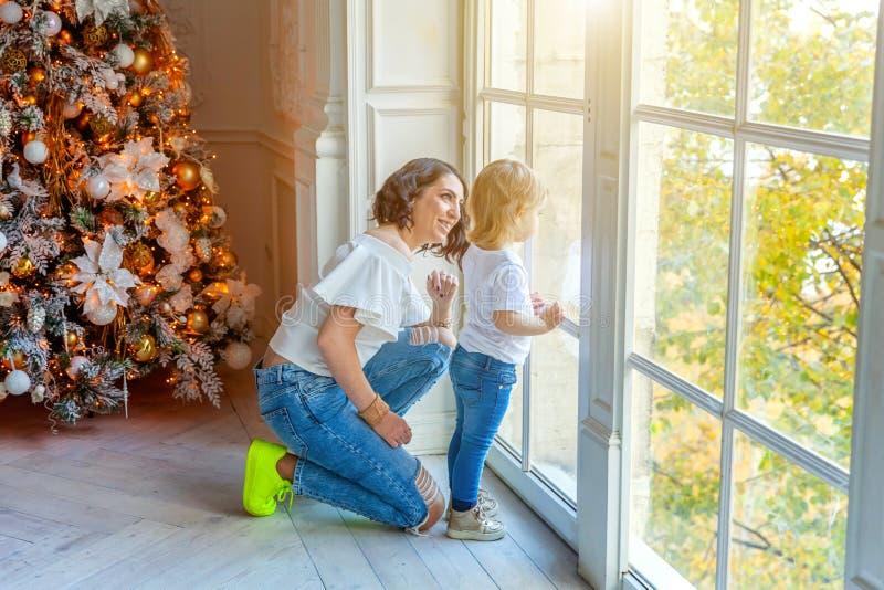 母亲和女儿在大窗口和圣诞树附近在家 库存照片