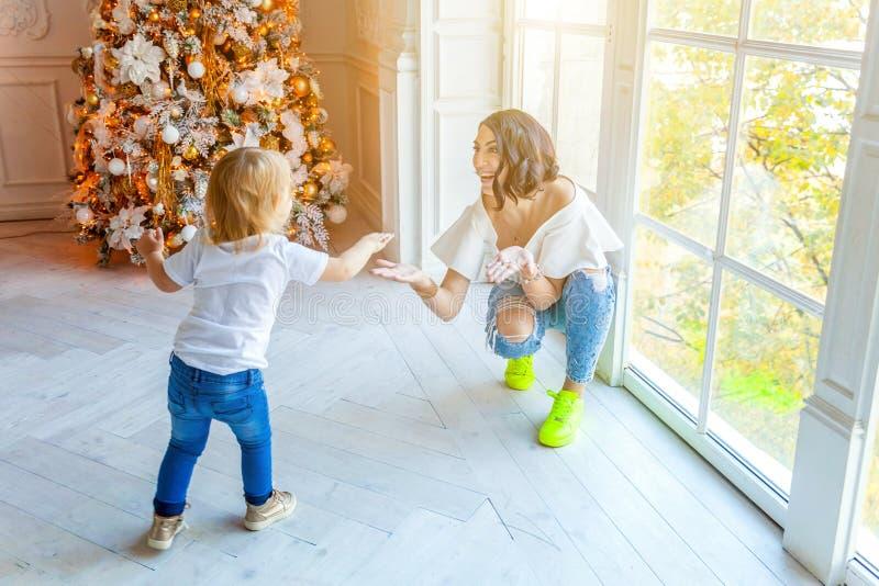 母亲和女儿在大窗口和圣诞树附近在家 免版税库存照片