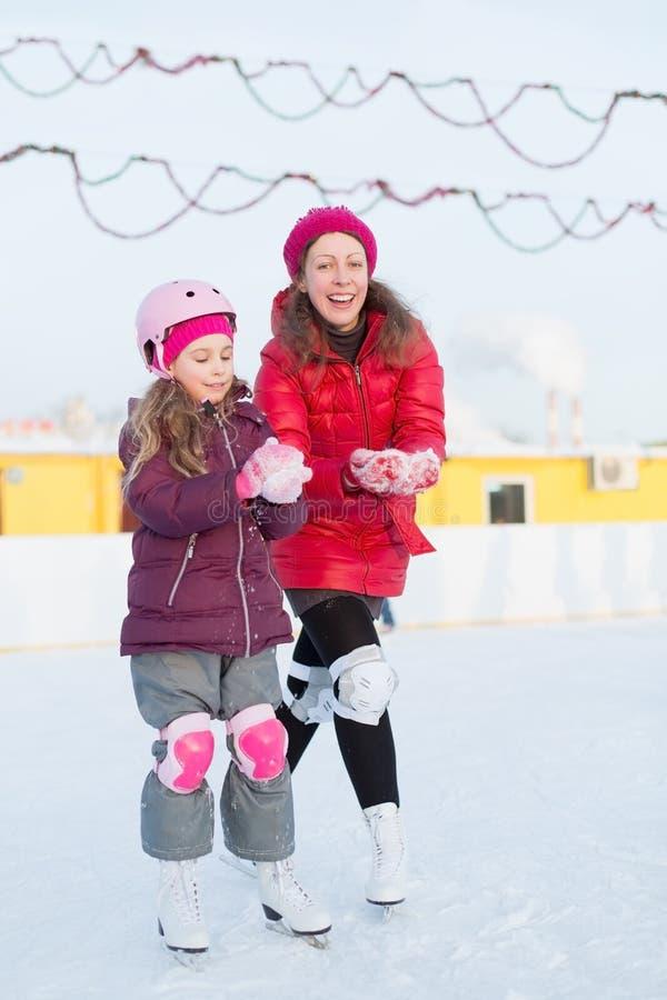 母亲和女儿在室外滑冰场铸造雪球 图库摄影