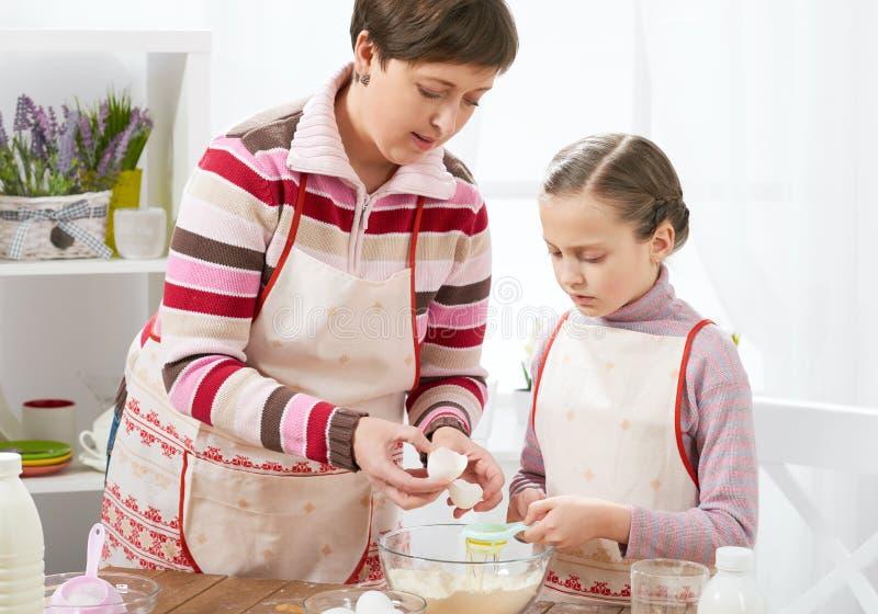 母亲和女儿在家烹调 内部的厨房,健康食物概念 库存照片