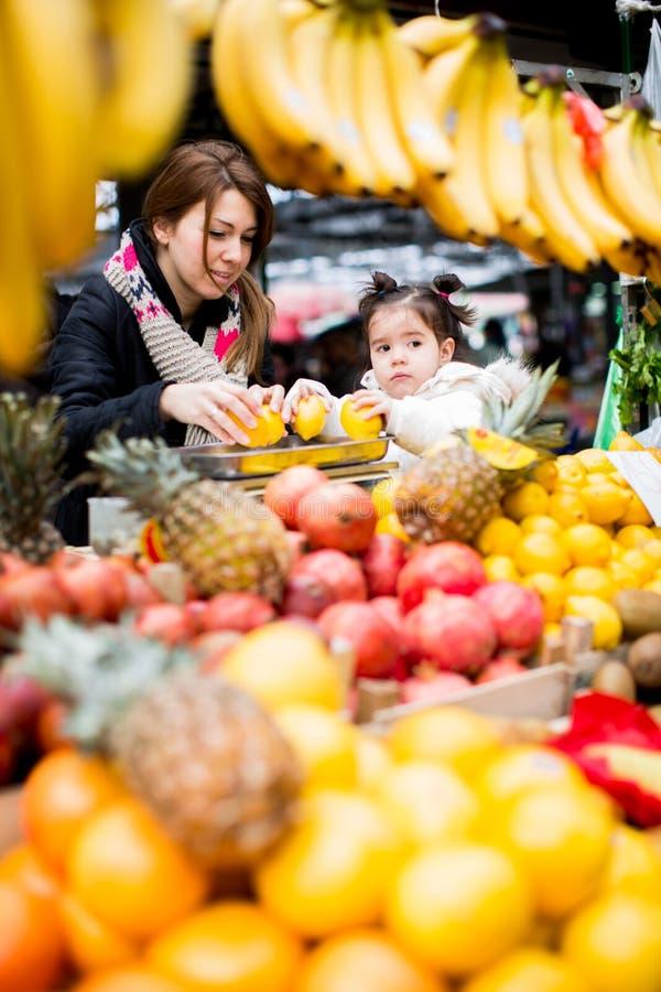 母亲和女儿在市场上 免版税库存图片