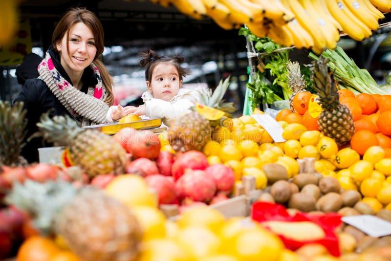 母亲和女儿在市场上 库存照片
