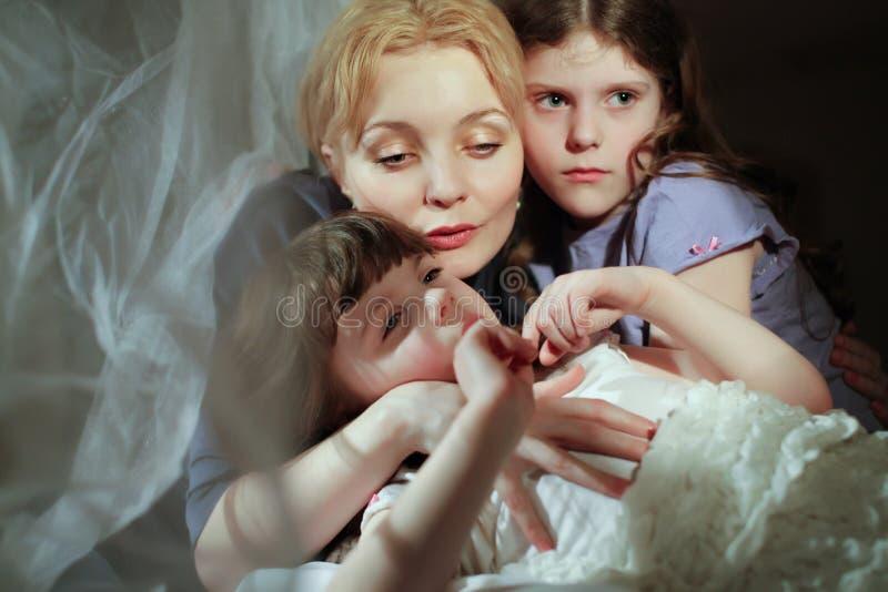 母亲和女儿在床上。 免版税库存照片
