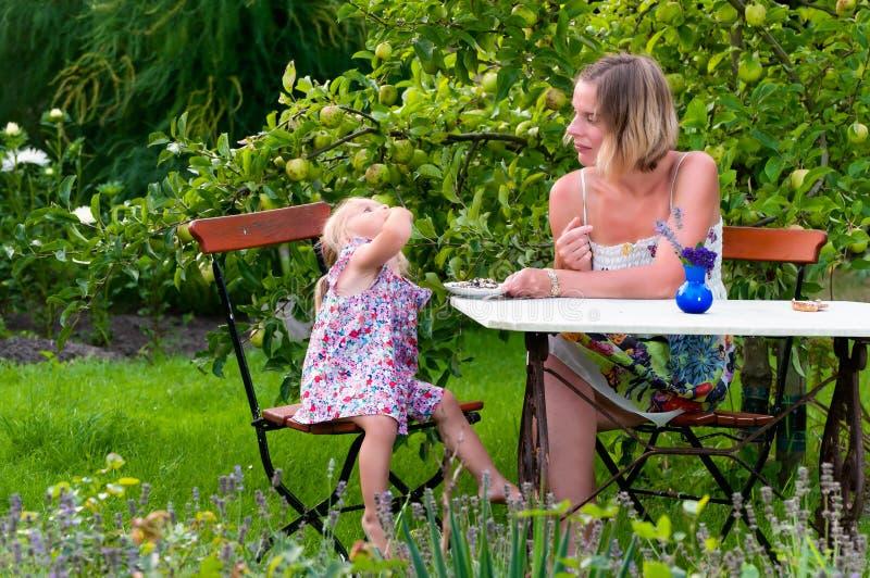 母亲和女儿在庭院里 库存图片