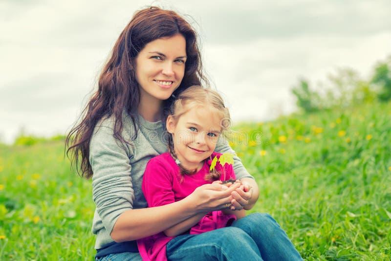母亲和女儿在手上的拿着一点绿色植物 免版税图库摄影