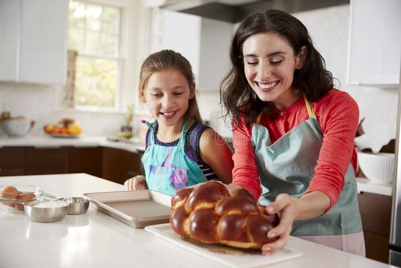母亲和女儿在有新近地被烘烤的鸡蛋面包的厨房里 图库摄影