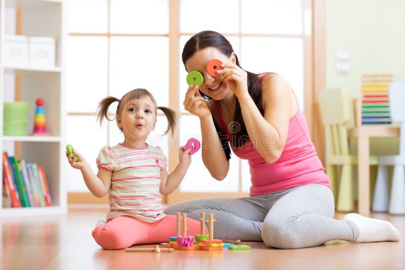 母亲和女儿在有的地板上使用乐趣消遣 免版税库存照片