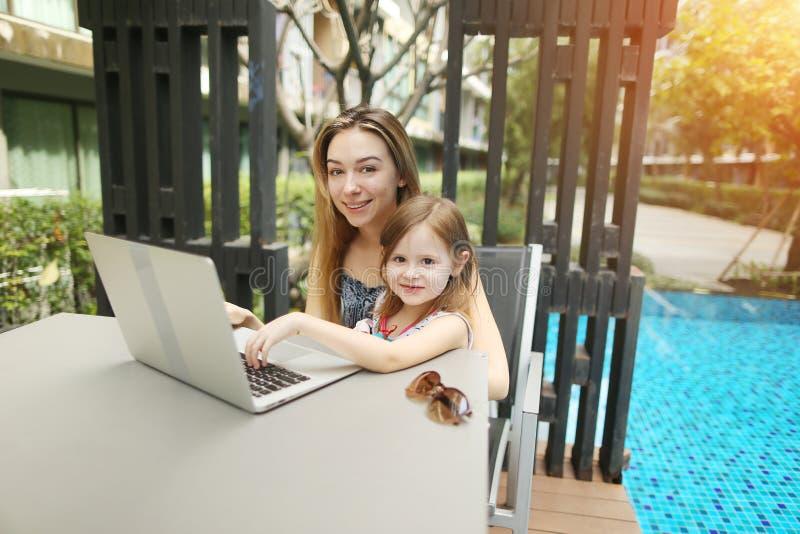 母亲和女儿在游泳池背景的用途膝上型计算机画象在晴天 免版税库存图片