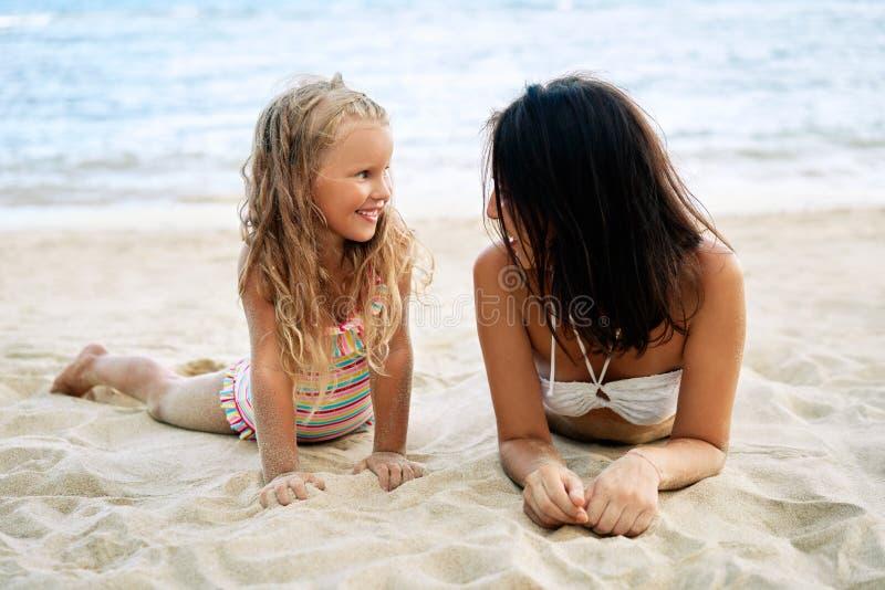 母亲和女儿在热带海滩放松在暑假 图库摄影