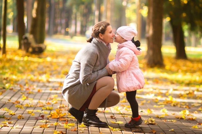 ?? 母亲和女儿在秋天公园 有孩子的母亲在室外 免版税库存照片