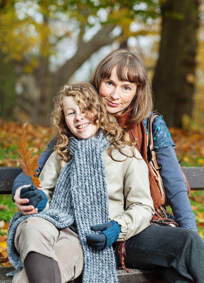 母亲和女儿在秋天公园 库存图片