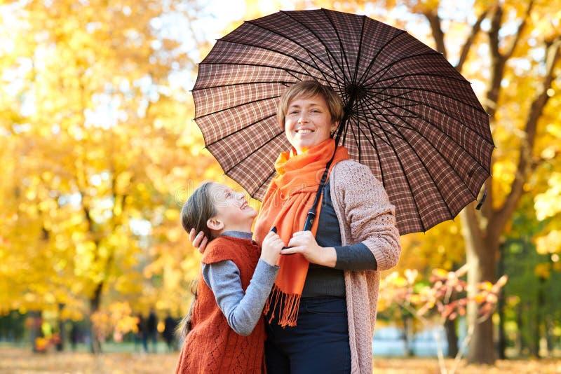 母亲和女儿在秋天城市公园 人摆在伞下 孩子和父母微笑着,使用并且havi 库存照片