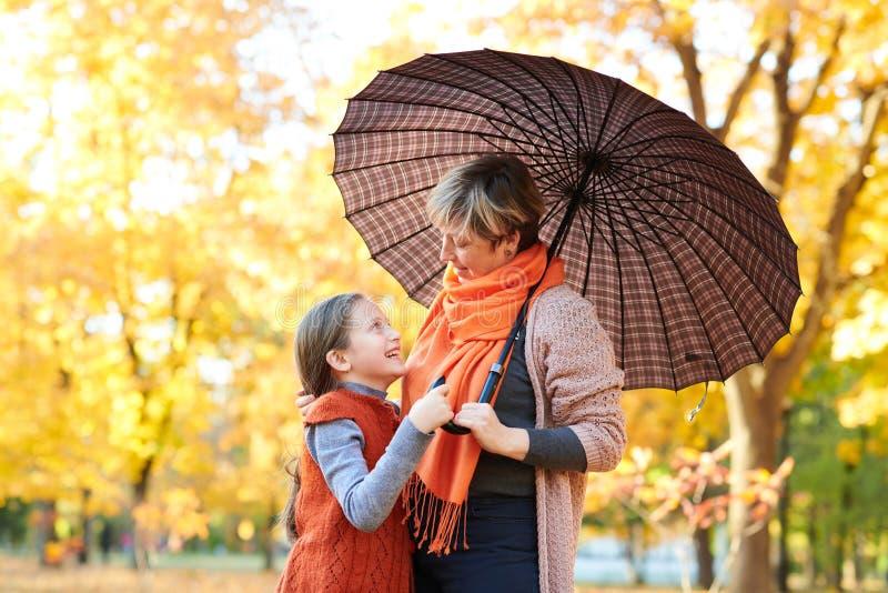 母亲和女儿在秋天城市公园 人摆在伞下 孩子和父母微笑着,使用并且havi 免版税图库摄影