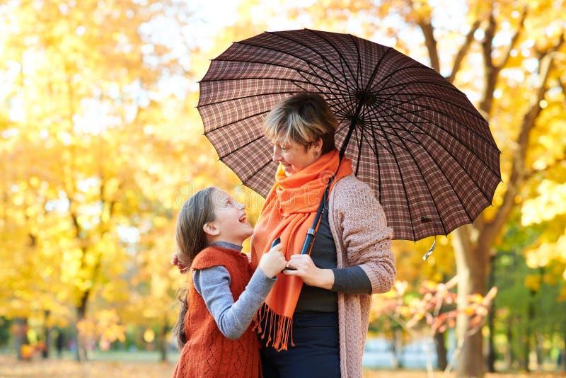 母亲和女儿在秋天城市公园 人摆在伞下 孩子和父母微笑着,使用并且havi 免版税库存图片