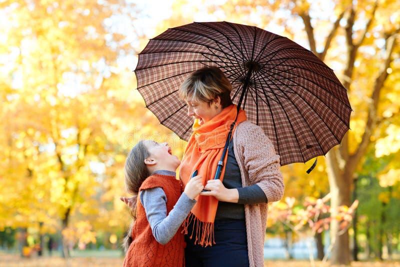母亲和女儿在秋天城市公园 人摆在伞下 孩子和父母微笑着,使用并且havi 免版税库存照片