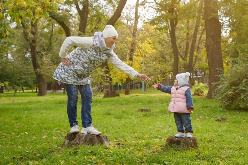母亲和女儿在parkland的树桩站立和给手往互相在一温暖的秋天天 免版税库存照片