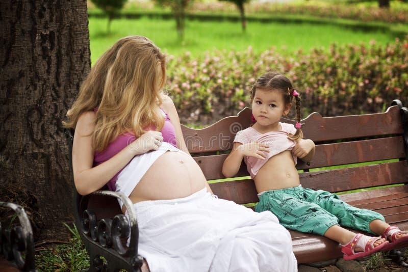 母亲和女儿坐公园长椅 免版税库存照片