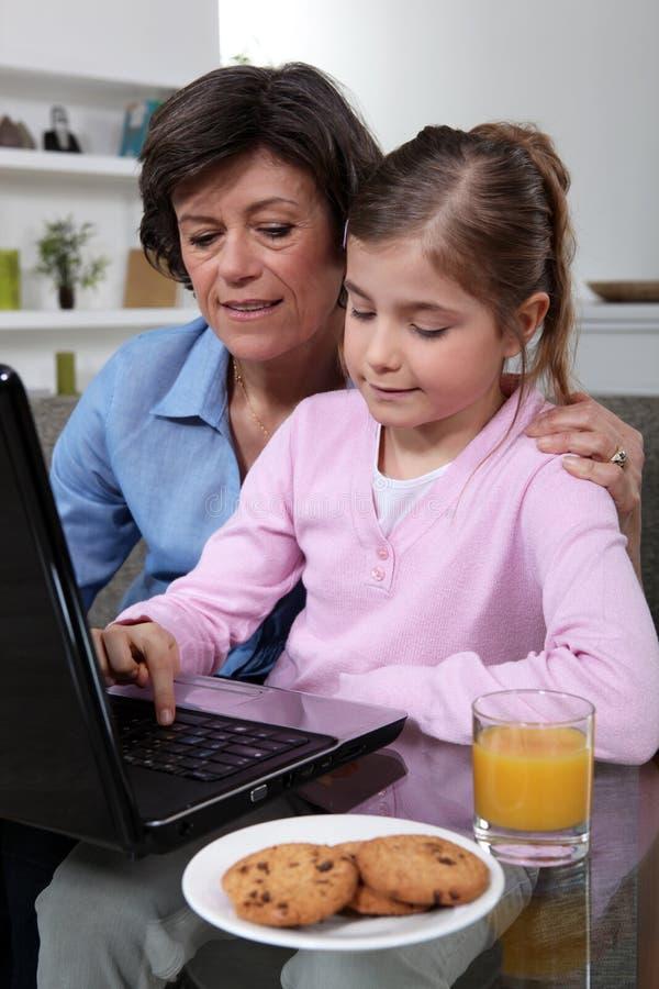 母亲和女儿坐在膝上型计算机 库存图片