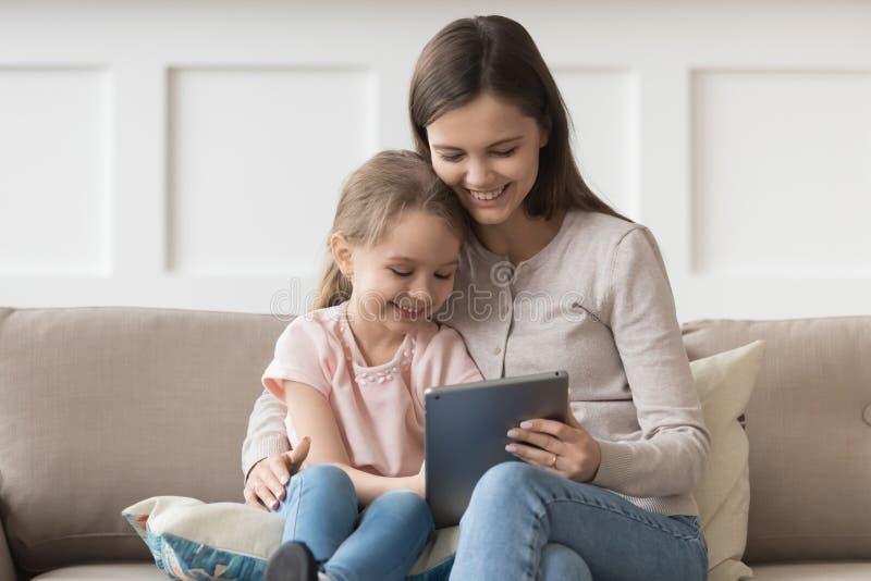 母亲和女儿坐有的长沙发乐趣用途片剂 免版税库存图片