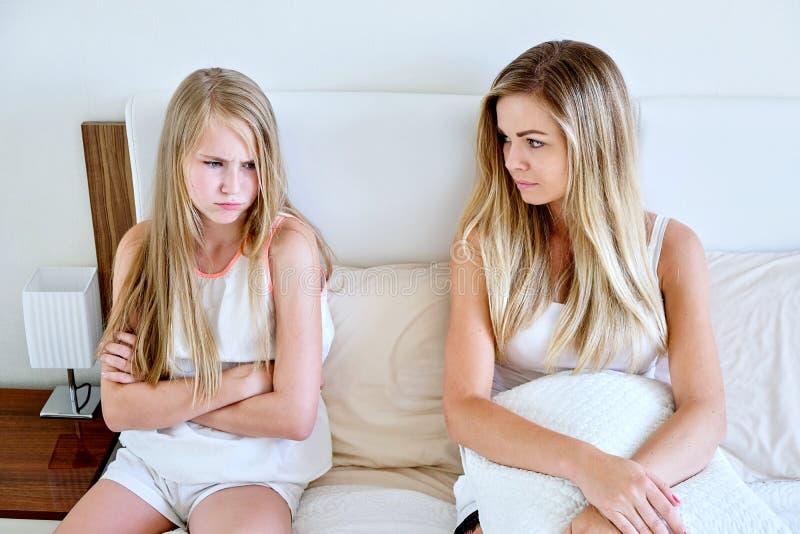 母亲和女儿坐看起来的床垫哀伤 库存照片