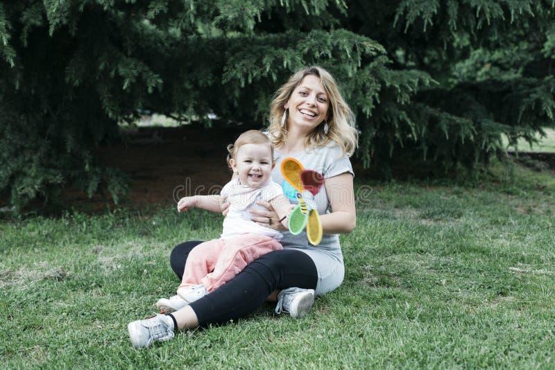 母亲和女儿坐草坪 免版税库存照片