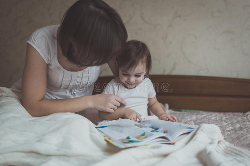 年轻母亲和女儿小孩阅读书坐床 免版税库存图片