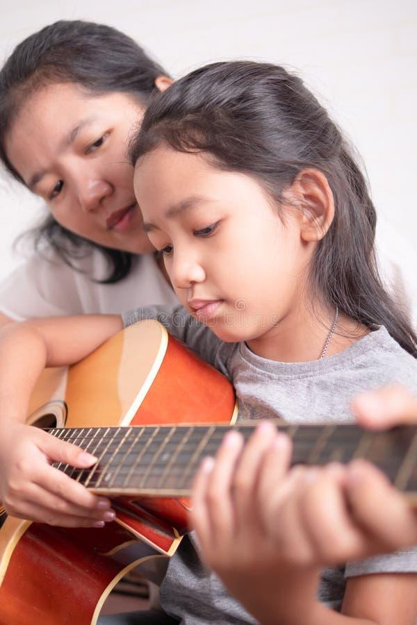 母亲和女儿弹吉他 库存照片