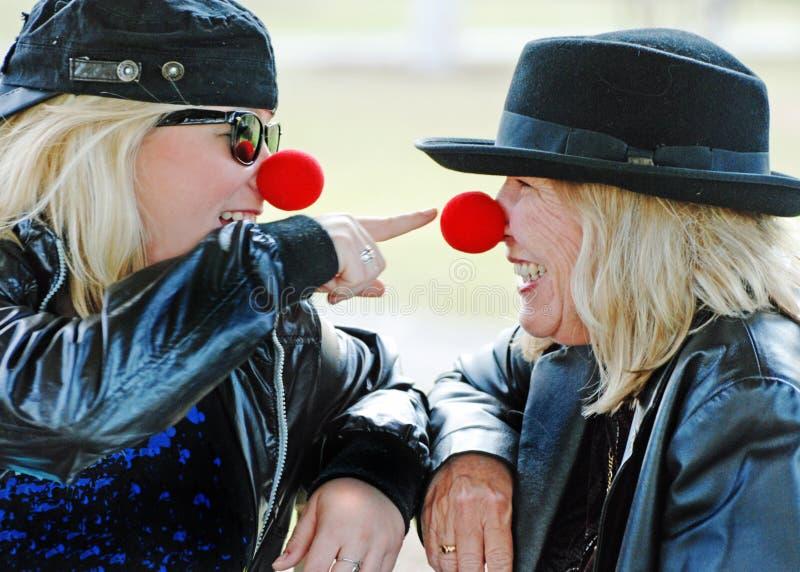 母亲和女儿微笑的一起笑获得乐趣 免版税库存图片