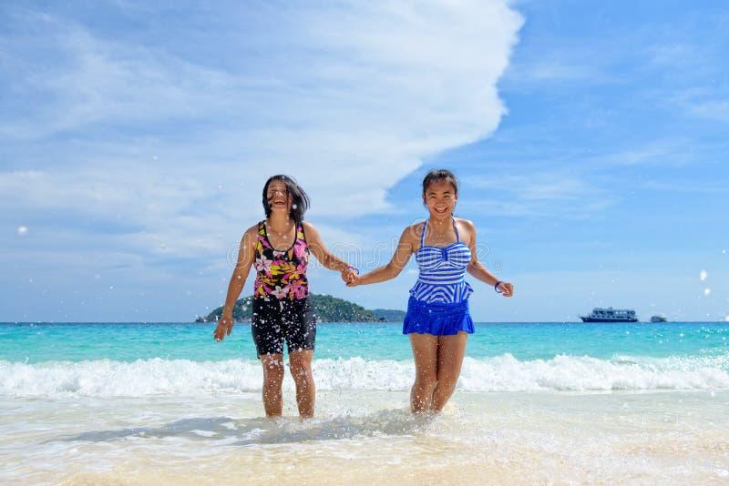 母亲和女儿愉快在海滩 库存图片
