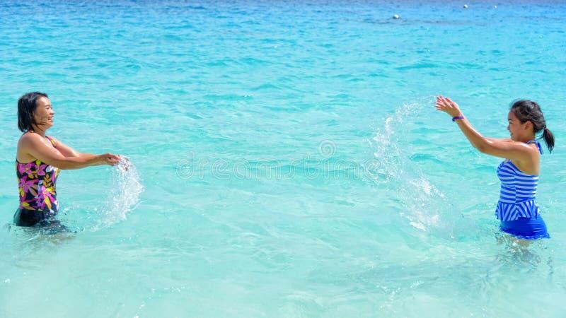 母亲和女儿愉快在海滩 免版税库存图片