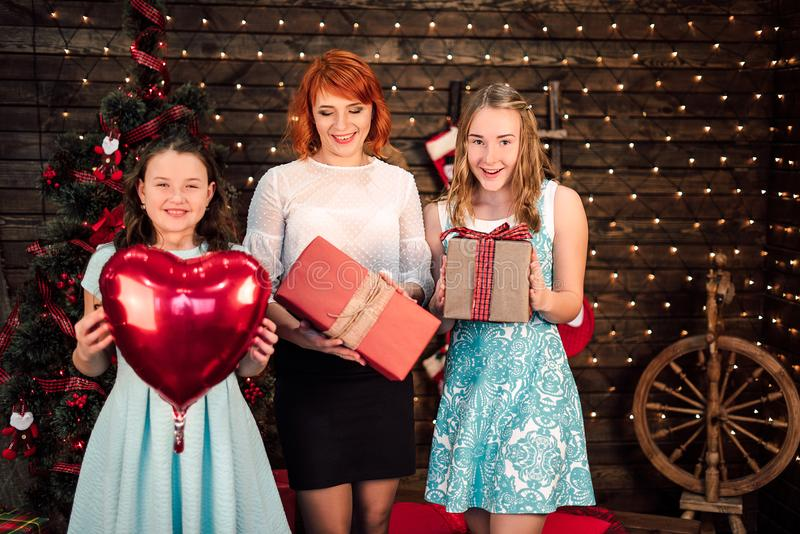 母亲和女儿愉快的家庭有圣诞节礼物的在圣诞树附近 被修饰的射击 免版税图库摄影