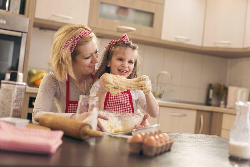 母亲和女儿揉的面团 免版税库存照片