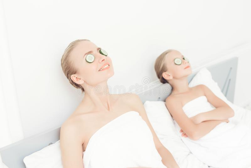 母亲和女儿有一天温泉 他们在与切片的白色毛巾在他们的眼睛的黄瓜 免版税库存照片