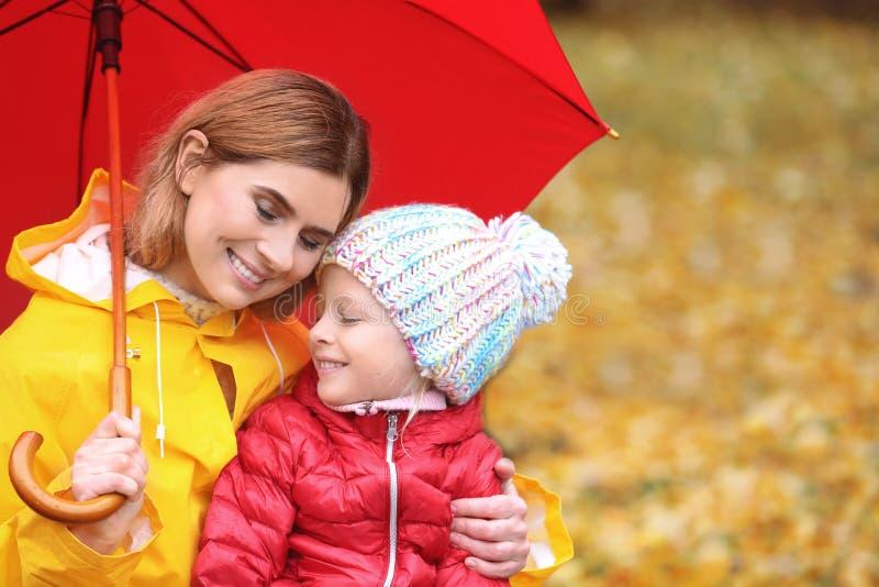 母亲和女儿有伞的在秋天公园 库存图片