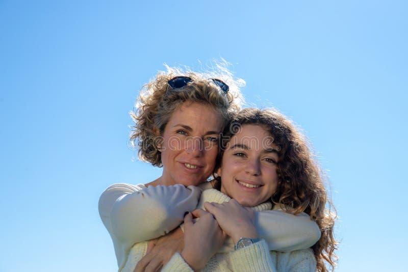 母亲和女儿有天空蔚蓝的在背景中 库存照片