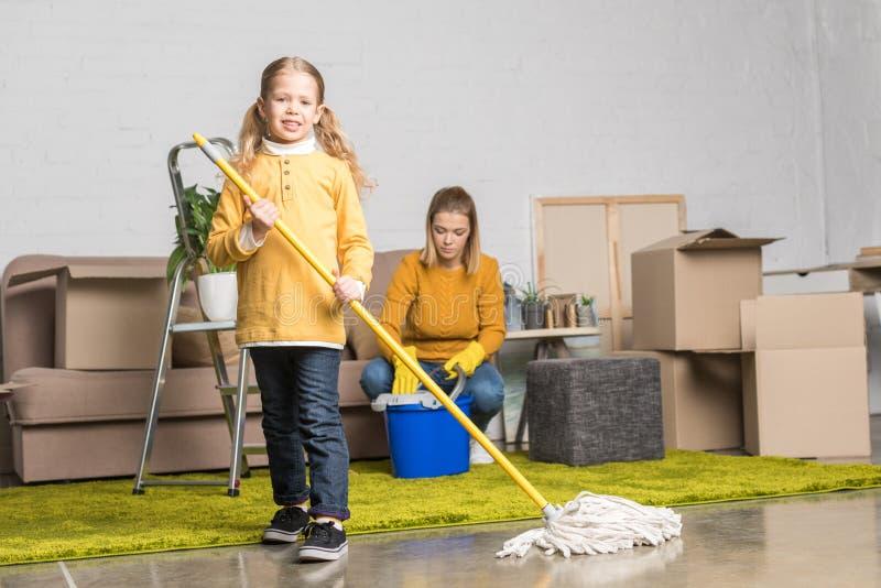 母亲和女儿有拖把和桶一会儿的洁净室 库存图片