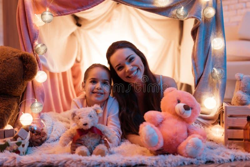 母亲和女儿有玩具熊的在枕头在晚上在家后安置 图库摄影