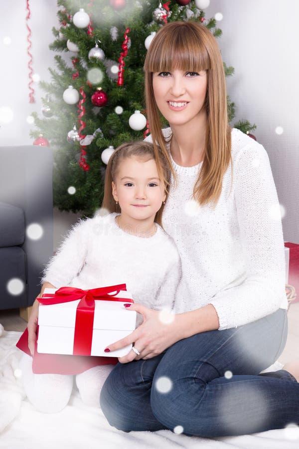 年轻母亲和女儿有礼物的在圣诞树前面 免版税库存图片