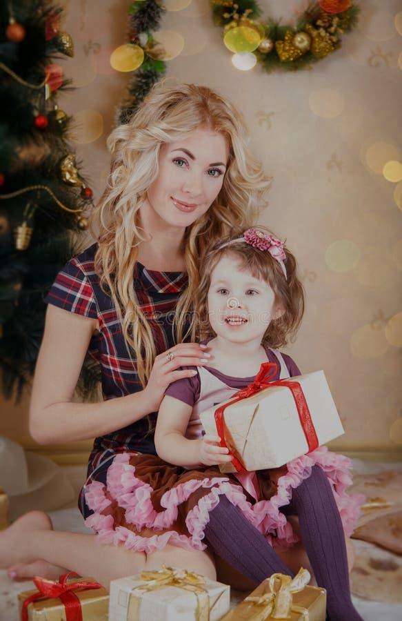 母亲和女儿有礼物箱子的在圣诞树附近 库存照片