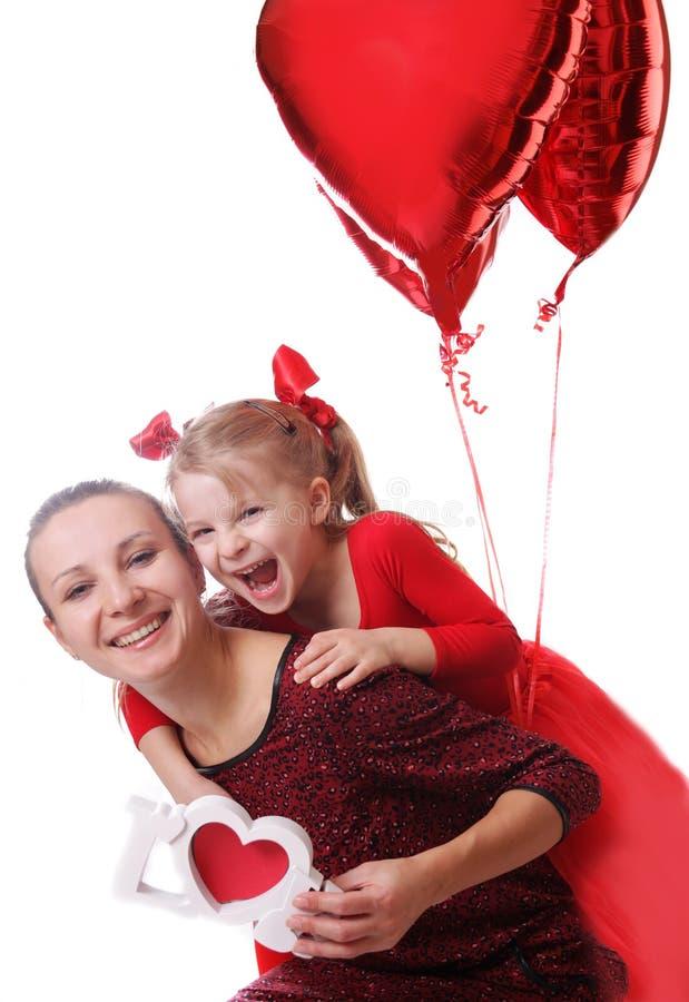 母亲和女儿有红色词爱和气球的 免版税图库摄影