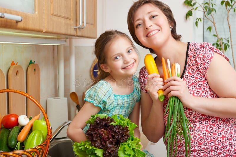 母亲和女儿有菜和新鲜水果的在厨房内部 父母和孩子 健康概念的食物 库存图片